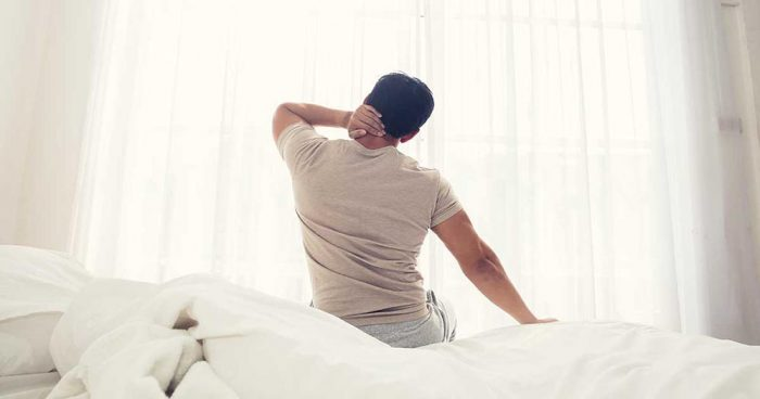 Image of a man's back as he sits on the edge of the bed, holding his neck
