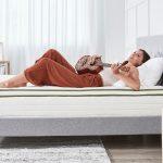Woman lying on back on bed playing a ukulele