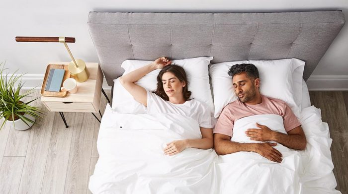 Man and woman back sleeping on grey aesthetic bed